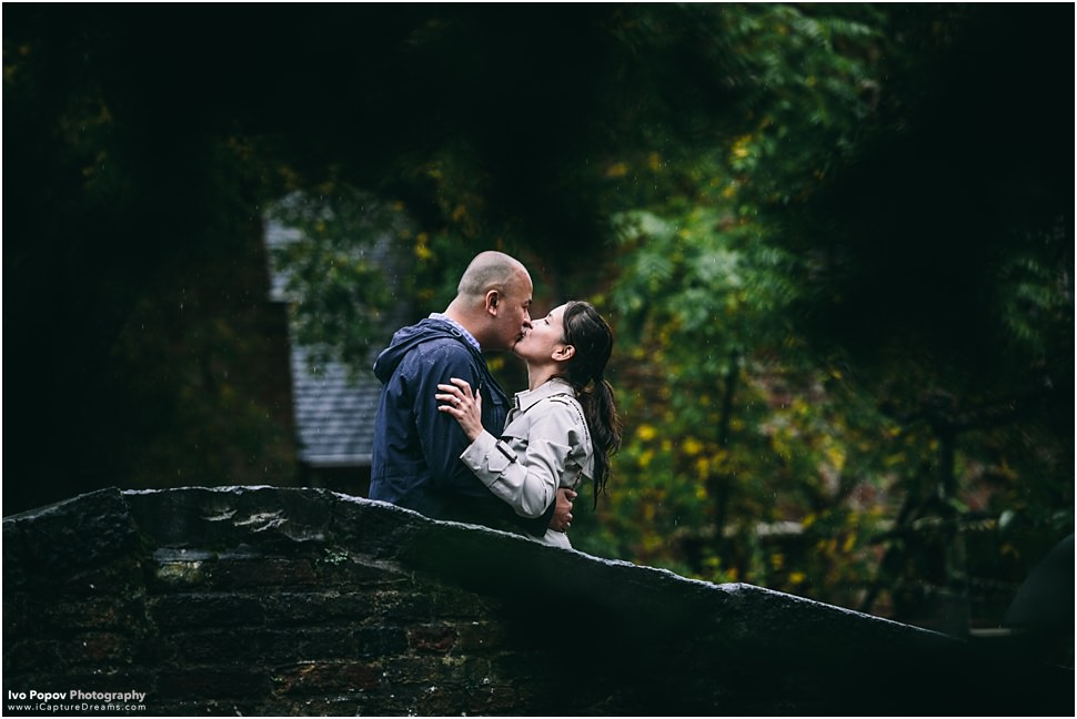 Romantic kiss on a bridge in Bruges during marriage proposal