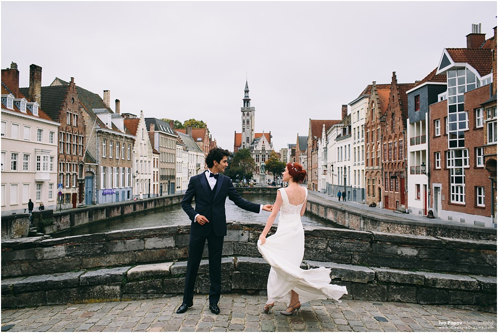 Bride and groom dancing on a bridge in Bruges