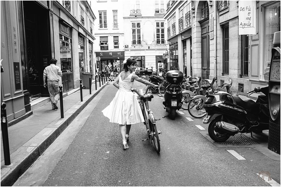 Beautiful and fun bride in Paris riding a bike