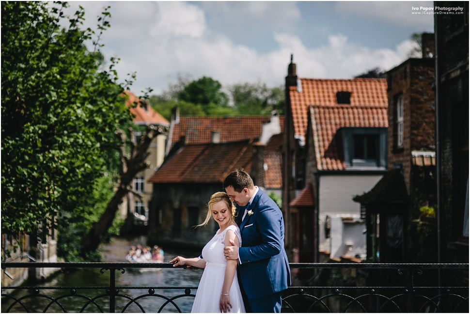 Happy newlywed couple on a bridge in Bruges