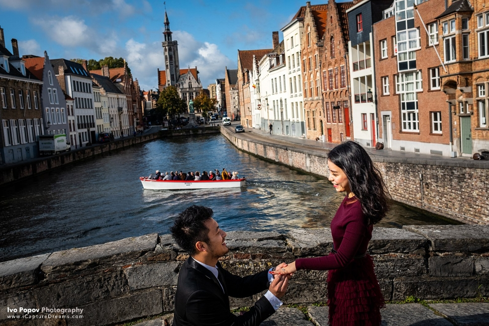 Girl excepts wedding ring on a bridge in Bruges